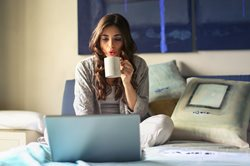 young woman sitting on a bed blowing on hot coffee and looking at her laptop