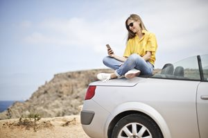 Young woman sitting on back of car looking at a phone at the beach