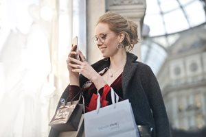 young woman carrying shopping bags and looking at her smart phone