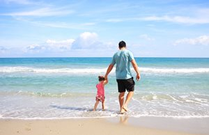 Father walking with toddler daughter on the sandy beach