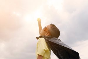 young boy with cape and sunglasses up pretending to fly