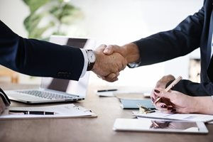 two businessmen shaking hands over a table