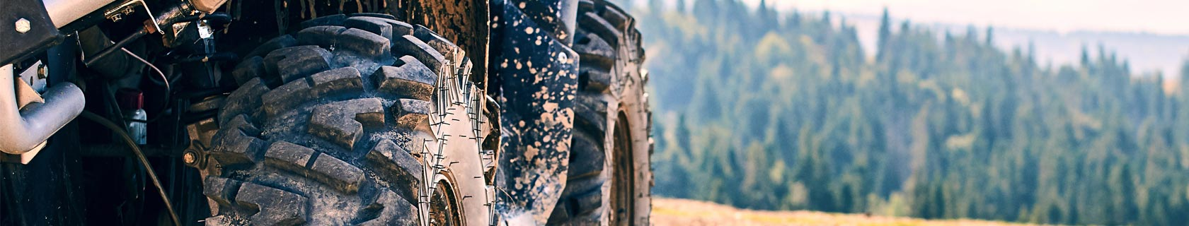 Close up of ATV tires covered in dirt and mud