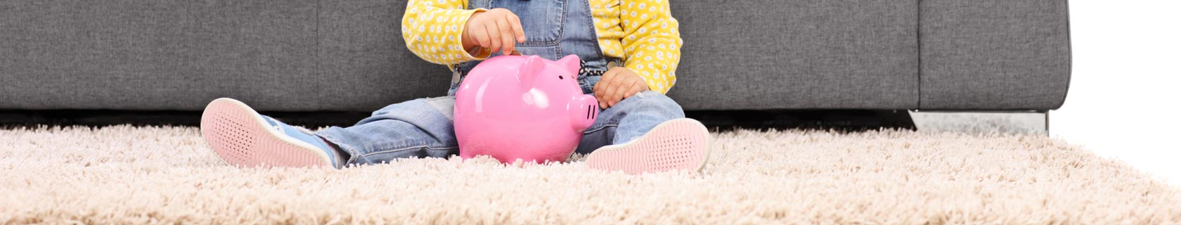 toddler in jean overalls putting a coin into a pink piggy bank